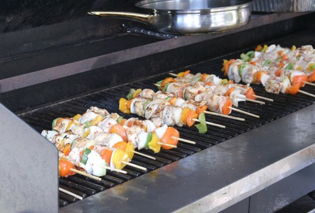 Chicken on skewers with vegetables cooks on an outdoor grill. Stock Photo