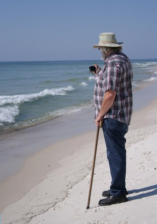 Mature Man with Camera on the Beach at Gulf Shores, Alabama, USA, at end of summer.