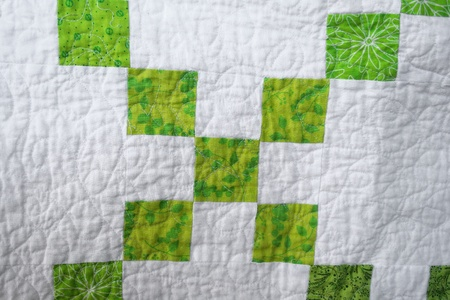 Handcrafted quilt of cotton fabric with machine stitched quilting for warmth and comfort. Stock Photo