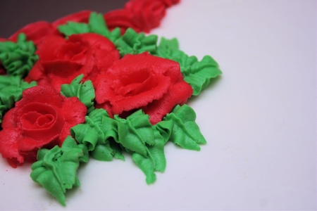 Close-Up view of buttercream frosting roses and leaves on a white cake. Stock Photo
