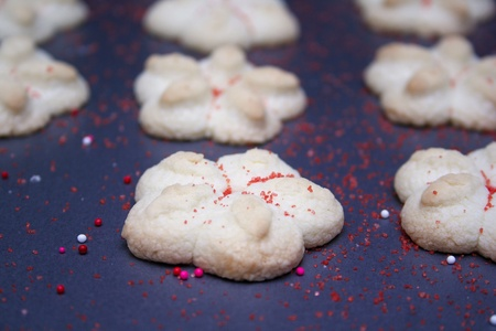 Sprtiz cookies with red sugar on a cookie sheet.