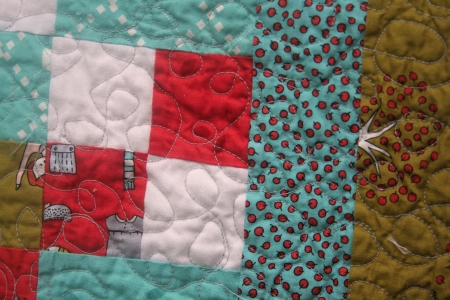 Close up view of a machine stitched, handmade patchwork quilt.