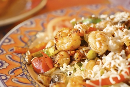 close up food: Grilled shrimp and scallop salad on a bed of shredded lettuce topped with white cheese at a Mexican restaurant.