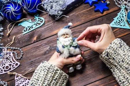 Girl makes Christmas gifts on a dark wooden table. Christmas decorations. Stock Photo