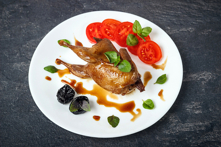 Baked quail with tomatoes, pomegranate, prunes and greens. A gla