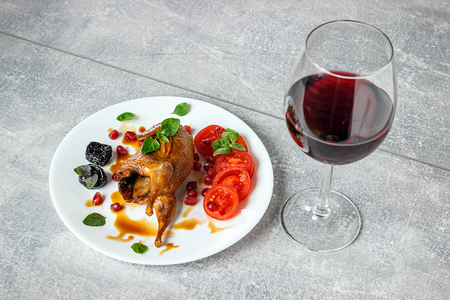 Baked quail with tomatoes, pomegranate, prunes and greens on a white plate. A glass of red wine.