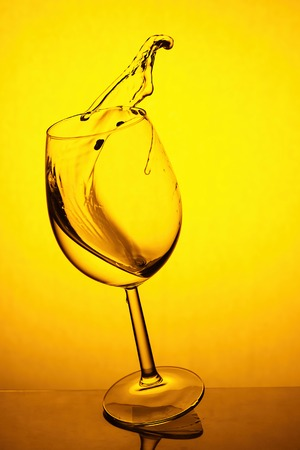 splash of white wine in a glass on a  yellow background
