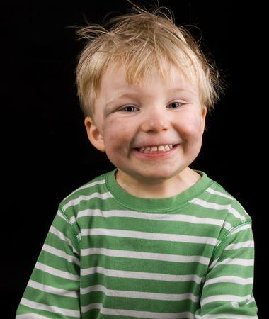 poco: Sonriente niño pequeño sobre fondo negro. Niño tiene un poco de suciedad, cabello rubio y ojos azules en su cara