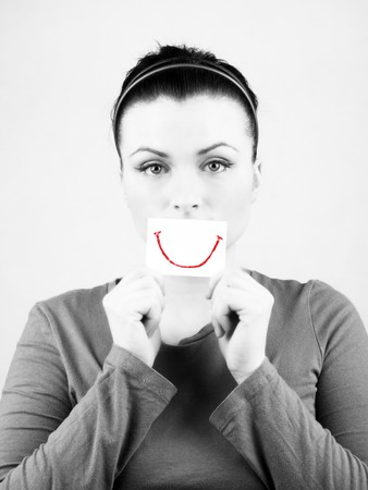 fake smile: Black and white portrait of beautiful sad woman with fake smile on white background.