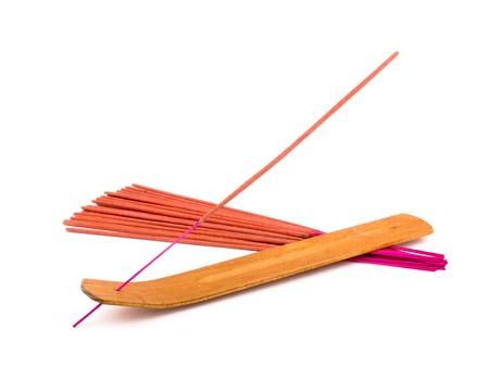 Orange incense in wooden holder on white background photo