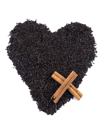 theine: Aromatic black tea leaves formed on heart on white background Stock Photo