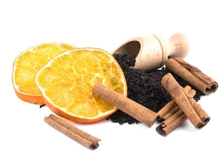 theine: Dry aromatic black tea leavs with cinnamon and orange on white background Stock Photo