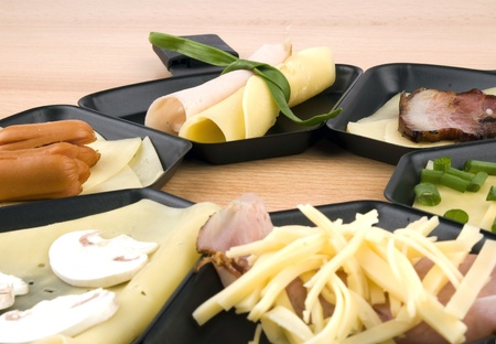Raclette pans with edam cheese and ham, bacon, mushroom, spring onion, coctail sousages on wooden table photo