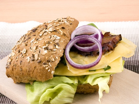 Granary bread with lettuce, raclette cheese, bacon and red onion on wooden chopping board photo