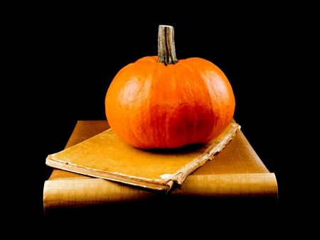 Studio shot of large halloween pumpkin with two old books on black background. Stock Photo - 11310386