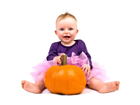 Cute little baby girl in pink tutu skirt with large pumpkin on white background photo