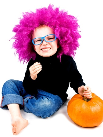 Cute little boy in big pink wig with halloween pumpkin making funny face on white background photo