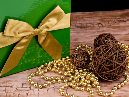 Big green gift box with golden ribbon and christmas ornaments on wooden table photo
