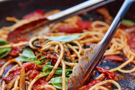 A rustic prepared meal of freshly cooked spaghetti, spicy tomato and fragrant green basil. Prepared quickly to share with the family and friends.
