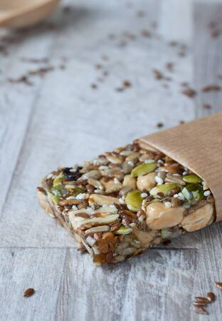 Superfood breakfast homemade bars with oats and seeds, on white wooden background