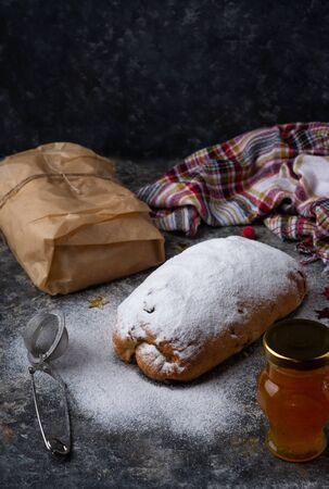 Traditional European Christmas pastry, home baked stollen, with powder sugar. Dark background.