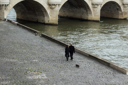 seine: A couple walks their dog along river Seine in Paris.