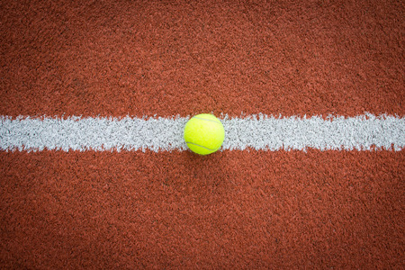 borderline: Yellow ball on the white marking line of a brick red court Stock Photo