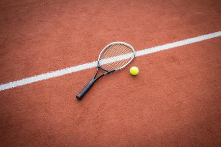 raqueta de tenis: Raqueta de tenis cerca de una bola amarilla en una cancha de ladrillo rojo