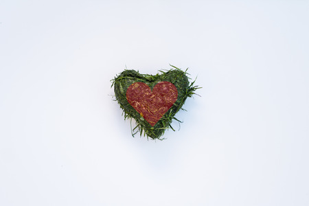 cut the grass: Heart shaped out of fresh cut grass with red heart graphic on top, over white background Stock Photo