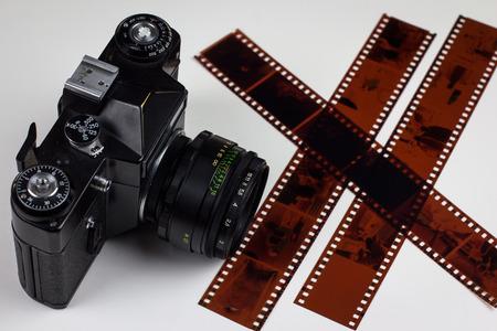 analogue: Analogue film photo camera with three filmstrips near Stock Photo