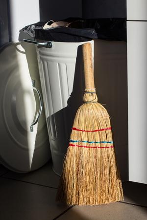 dumpster: Straw broom near dumpster