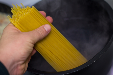 boiling: Hand puts spagetti in boiling water pot