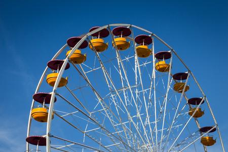 fairground: Ferris wheel ride at fairground over blue sky