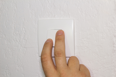 fingers: Fingers push electrical switch Stock Photo