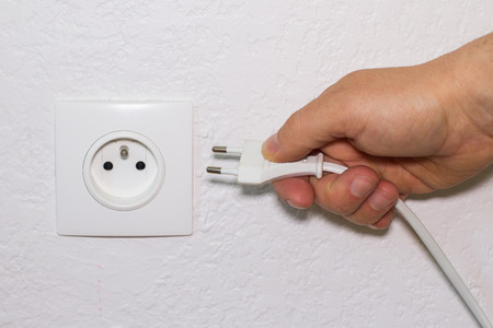 wall socket: Hand plugs electrical cord in white wall socket