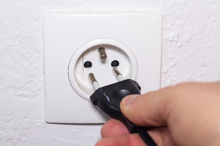 wall socket: Hand plugs power cord in wall socket Stock Photo