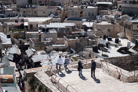 Jerusalem, Israel - March 17th, 2018: People walk the rooftops of Jerusalems Old City, in Israel.