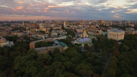 Panoramic view modern city on evening sky landscape. Drone view city architecture on colorful sky background. Golden domes christian churches in city structure