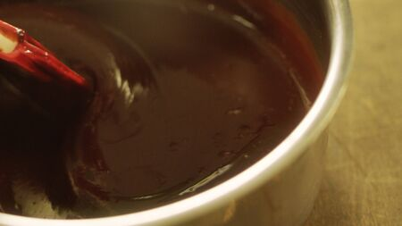 Closeup liquid chocolate making at home in slow motion. Macro of stirring hot chocolate with spatula. Mixing melted chocolate by spatula for cooking chocolate dessert.