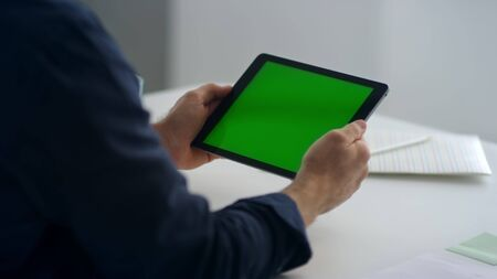 Close up man hands holding tablet with green screen. Unrecognized business man reading letter on paddle cell with chroma key. Closeup of male professional looking pad screen in slow motion.