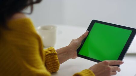 Close up businesswoman making video call on green screen tablet in slow motion. Back view business woman having video talk on green screen pad cell. Girl freelancer waving hands after conference call.