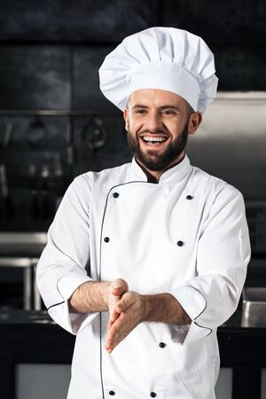 Chef man at kitchen restaurant. Portrait of smiling male chef at the professional kitchen. Happy beard man in white uniform and hat at kitchen cafe.