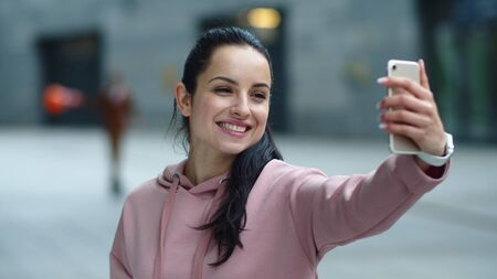 Close up smiling woman using mobile phone for video call online. Portrait of happy woman making video chat in smartphone. Cheerful girl talking online with cell phone in slow motion.
