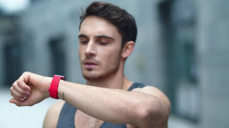 Closeup male athlete using smart clock outside. Portrait of fit man setting smart watch in slow motion. Sporty man checking fitness watch on outdoor training.