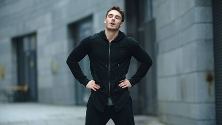 Fit man warming up outdoor in slow motion. Sporty man stretching neck on street training. Male athlete having fitness workout on urban street. Reklamní fotografie