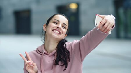 Close up cheerful woman posing for selfie photo on mobile phone. Portrait of happy woman showing victory sign for mobile picture. Smiling girl taking self portrait on mobile phone.