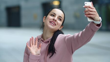 Close up smiling woman waving hand to smartphone camera. Happy girl using mobile phone for video chat outdoor. Portrait of cheerful woman call video online at urban street.