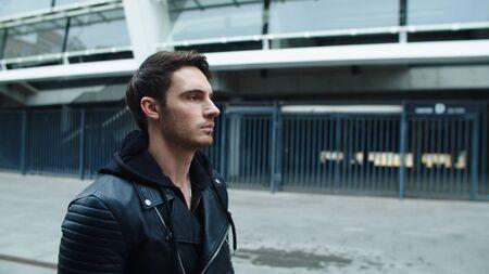 Rocker man walking street in black jacket in slow motion. Portrait of serious man going away from urban street. Close up of young man walking in empty city.