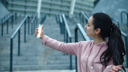 Beautiful woman making mobile photo outdoor. Sexy woman posing for selfie photo to smartphone. Funny girl showing victory sing for mobile picture. Joyful girl having fun with cellphone. Reklamní fotografie