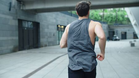 Fitness man running outdoor in slow motion. Back view of athlete man training run at street workout. Sportsman jogging on urban background.